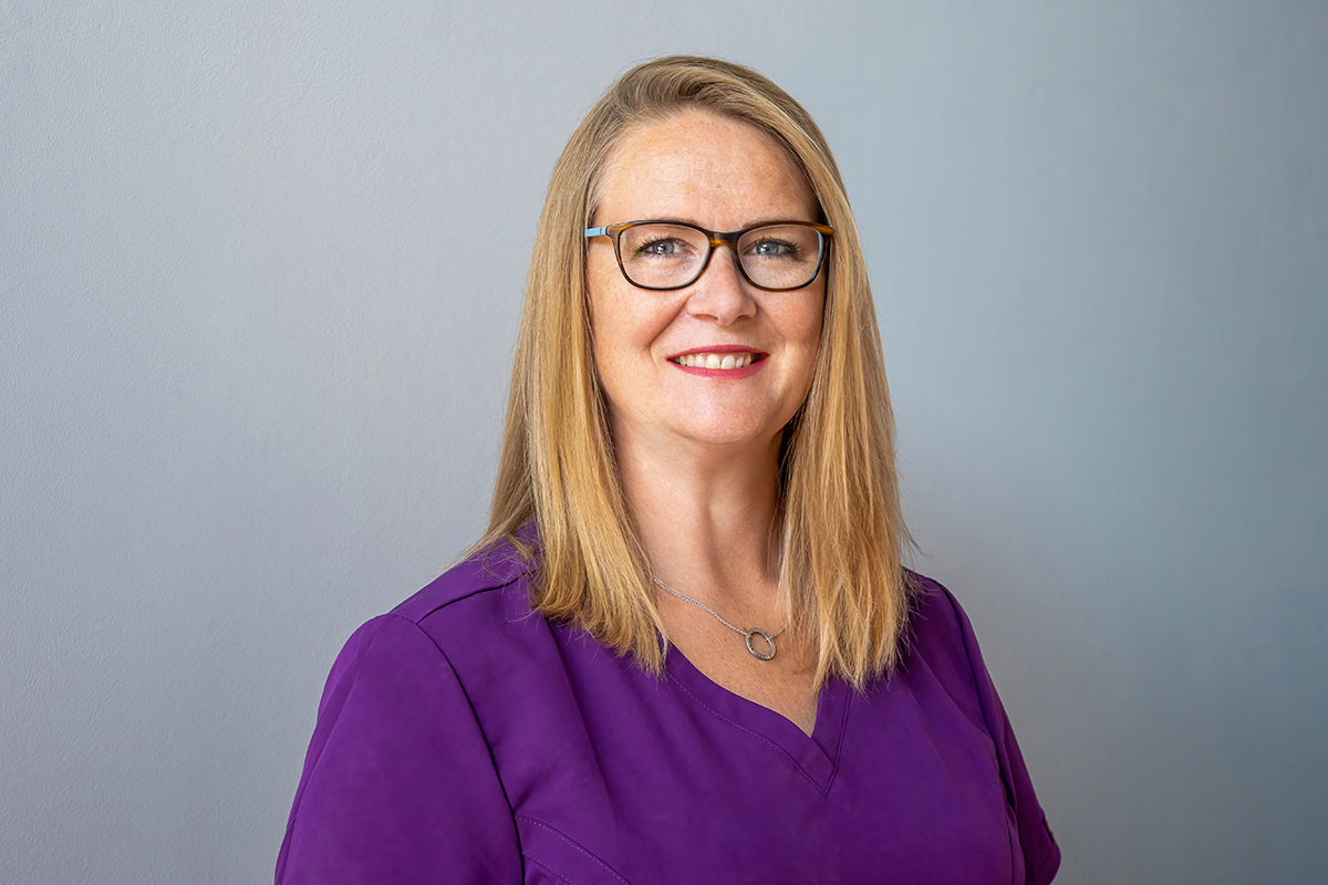 blonde lady wearing purple blouse and spectacles smiling at camera